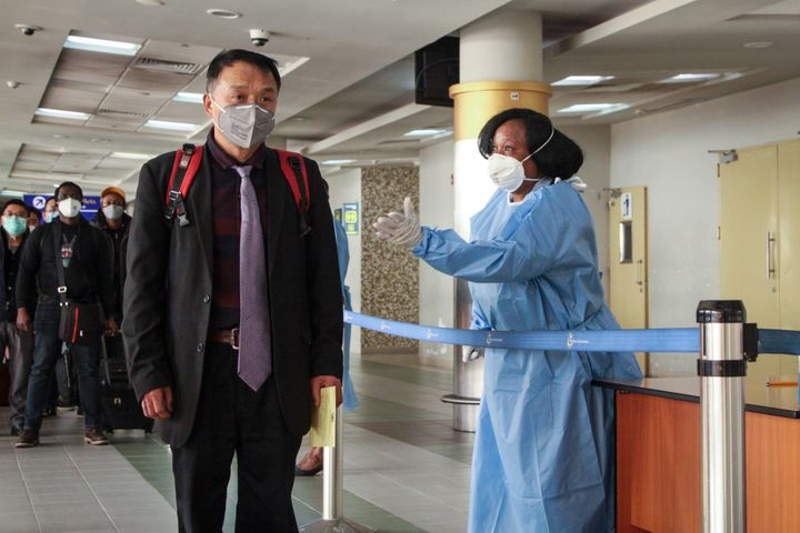 Passengers arriving from a China Southern Airlines flight from Changsha in China are screened for the new type of coronavirus