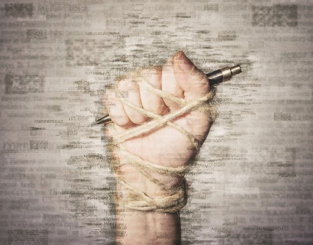 Hand with pen tied with rope, depicting the idea of freedom of the press or freedom of expression. Mixed