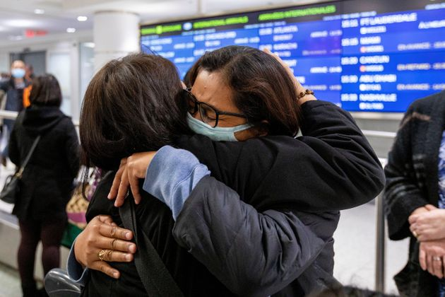 A woman hugs a relative at Toronto Pearson International Airport after arriving on a flight from Hong...