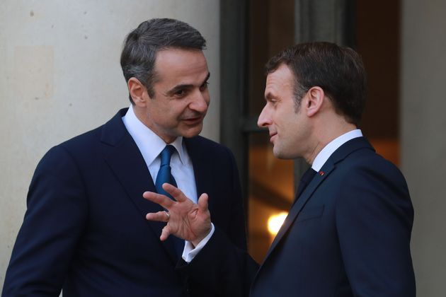French President Emmanuel Macron (R) and Greek Prime Minister Kyriakos Mitsotakis speak following their...