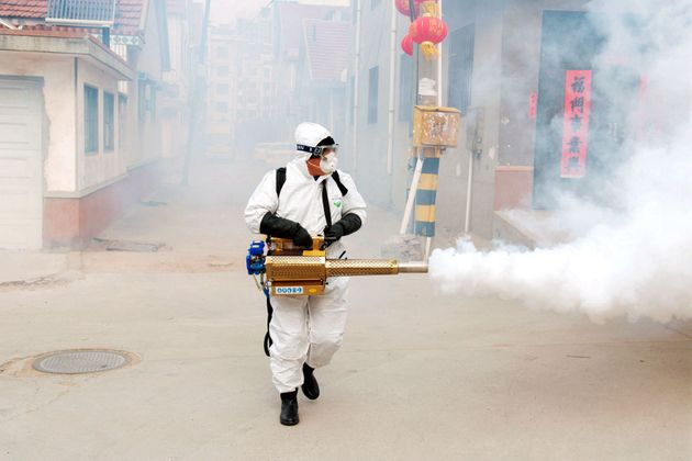 A Chinese volunteer wearing the protective clothing disinfects a street for prevention of the new coronavirus...