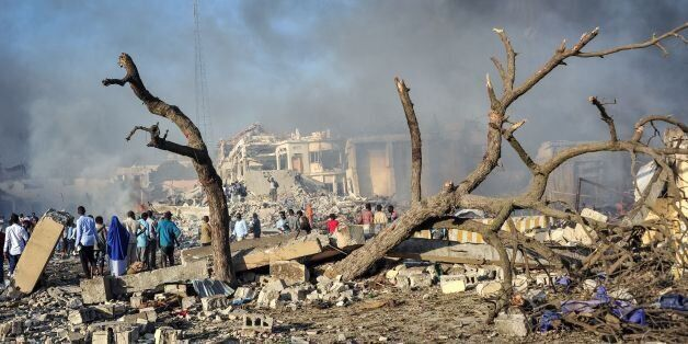 Men and Somalian soldiers arrive on the site to rescue victims of the explosion of a truck bomb in the...