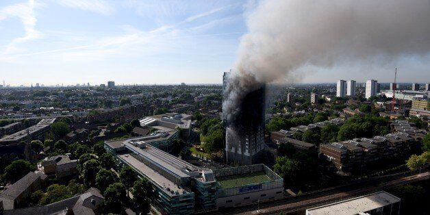 LONDON, ENGLAND - JUNE 14: Smoke rises from the building after a huge fire engulfed the 24 storey residential...