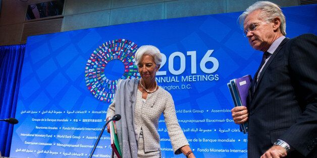 IMF Managing Director Christine Lagarde and IMF Spokesman Gerry Rice take their seats at the start of...