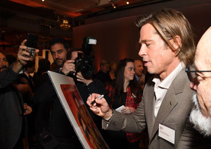 L'acteur américain Brad Pitt signe une affiche lors du dîner des nominés aux Oscars 2020, à Hollywood, le 27 janvier 2020.