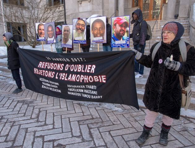 People hold photos of the victims during a vigil on Wednesday in Montreal to commemorate the third anniversary...
