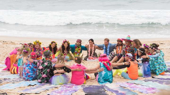 "Harry and Meghan in an ""anti-bad vibes circle"" with members of the surf and mental health group OneWave at Bondi Beach in Sydney, Australia, on Oct. 19, 2018."