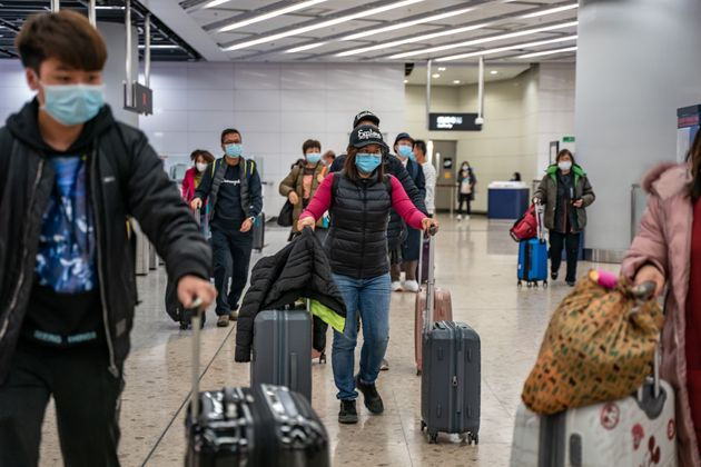 Travellers wearing protective masks exit the arrival hall at Hong Kong High Speed Rail Station on January...