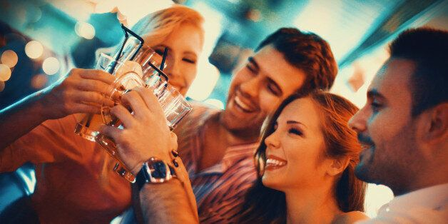 Group of young adult enjoying their night out in a club.Toasting with drinks,laughing and having casual conversation. Two couples on a double date.