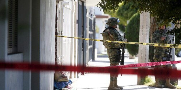 A soldier keeps watch outside the house where five people were shot dead during an operation to recapture...