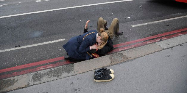 A woman assist an injured person after an incident on Westminster Bridge in London, March 22, 2017. REUTERS/Toby
