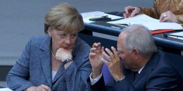 BERLIN, GERMANY - AUGUST 19 : German Chancellor Angela Merkel (L) speaks to German Finance Minister Wolfgang...