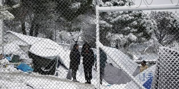 Migrants stand next to their tents at the Moria hotspot on the island of Lesbos , following heavy snowfalls...