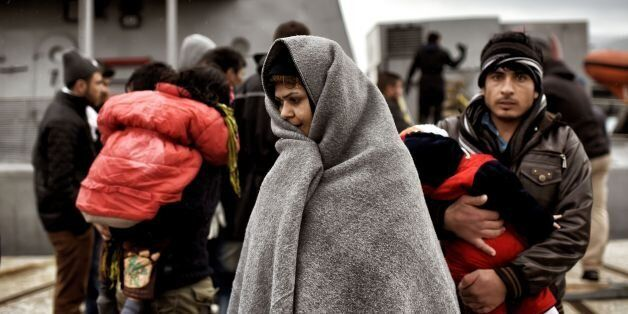 TOPSHOT - Refugees and migrants rescued by the Greek coast guard disembark from a ship upon their arrival...