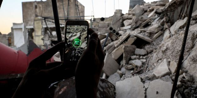 A Syrian gamer uses the Pokemon Go application on his mobile to catch a Pokemon amidst the rubble in...