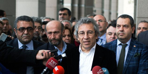 Can Dundar, the editor-in-chief of opposition newspaper Cumhuriyet, second right, and Erdem Gul, the...