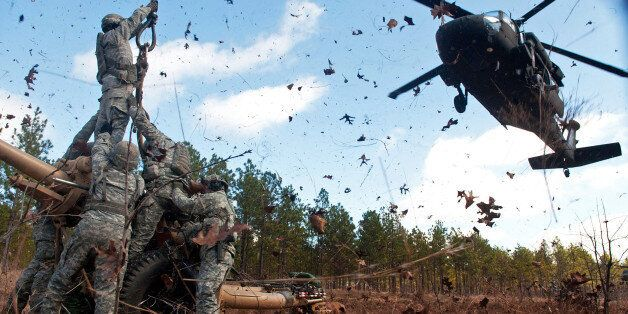 Leaves and twigs are whipped into the air by the rotor wash of UH-60 Black Hawk helicopter as soldiers...