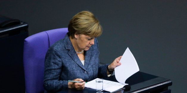 German Chancellor Angela Merkel reads documents as she attends a debate at the German parliament prior...