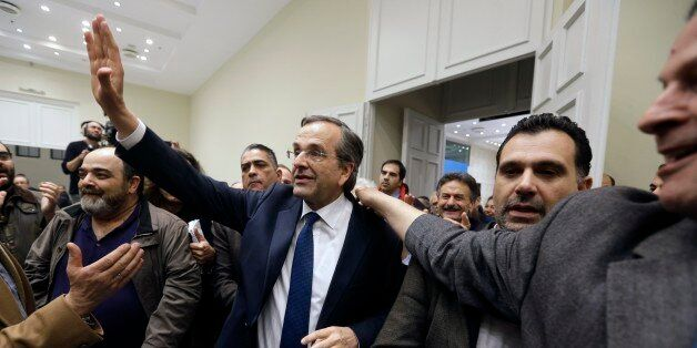 Greece's Conservative Prime Minister Antonis Samaras waves to his supporters as he arrivess at Zappeio...