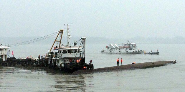 Chinese rescue boats are seen alongside a capsized passenger ship carrying more than 450 people which...
