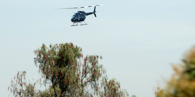A Federal Police helicopter overflies on December 4, 2013 the place in Tepojaco, Hidalgo state, where...