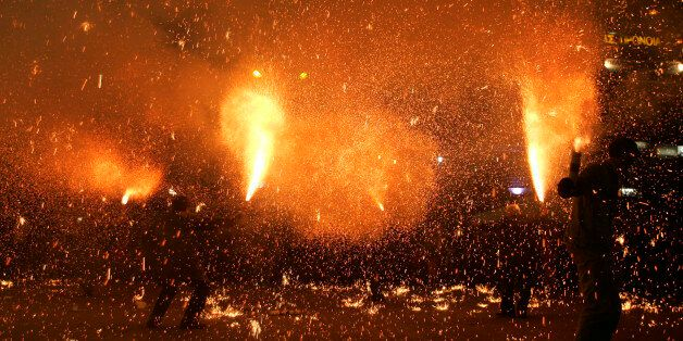 Revelers hold flares during pre-Easter celebrations in the city of Agrinio, western Greece, late Good...
