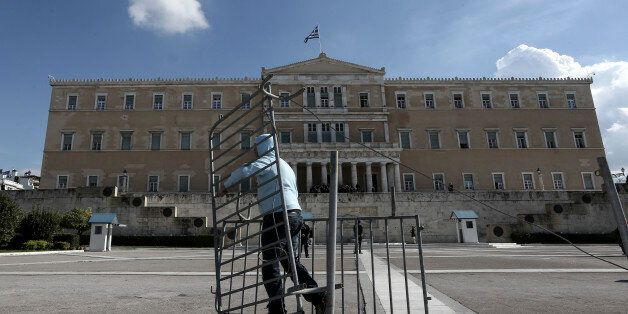 Following instructions from Greece's new left-wing public order minister, a worker removes crowd barriers...