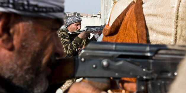 In this Wednesday, Nov. 19, 2014 photo, fighters from the Free Syrian Army, left, and the Kurdish People's...