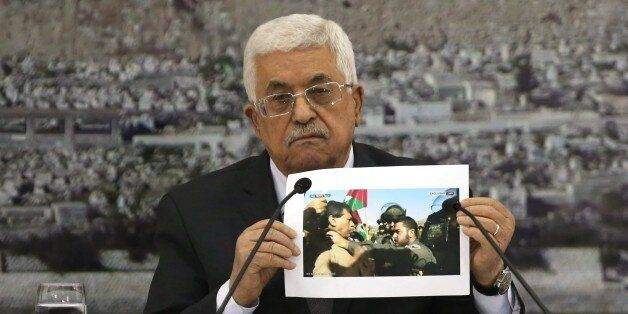 Palestinian President Mahmoud Abbas holds up a picture of senior Palestinian offical Ziad Abu Ein a in...