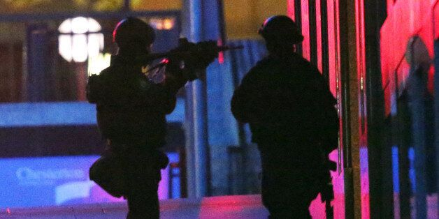 Armed tactical response officers enter the building after shots were fired during a cafe siege in the...