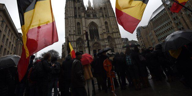Onlookers wave Belgium flags as the coffin arrives during the funeral of late Belgium Queen Fabiola of...