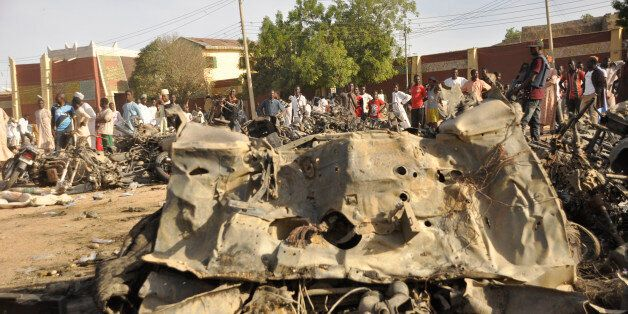 People gather at the site of a bomb explosion in Kano, Nigeria, Friday Nov. 28, 2014. An explosion tore...