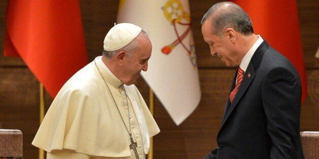 Turkish President Recep Tayyip Erdogan (R) shakes hands with Pope Francis following their joint press...