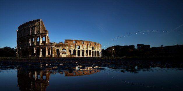 The Colosseum reflects in the water on November 21, 2014 in Rome. AFP PHOTO / FILIPPO MONTEFORTE (Photo...