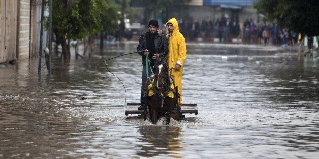 Palestinian men in a horse cart make their way through a flooded street during heavy rains in Gaza City...