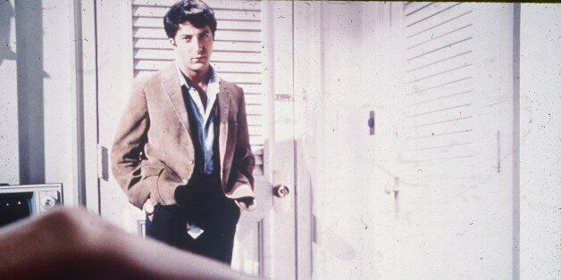 1967: American actor Dustin Hoffman looks down at the leg of actor Anne Bancroft, as Mrs. Robinson, in...