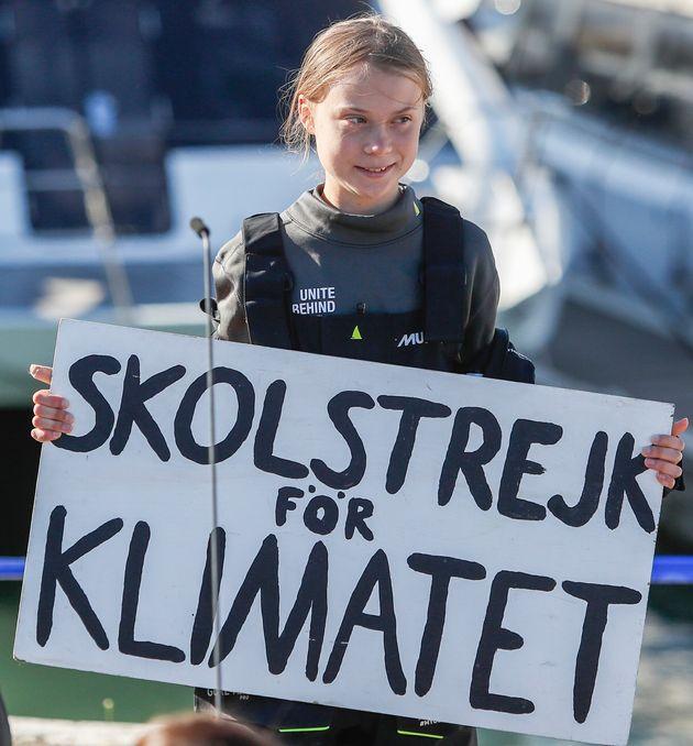 La militante pour le climat Greta Thunberg tient une bannière