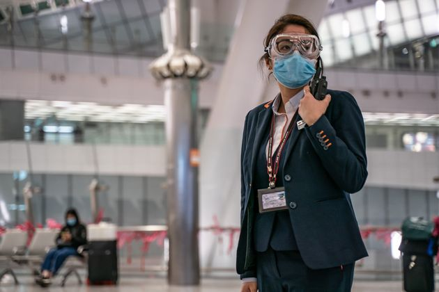 HONG KONG, CHINA - JANUARY 29: A MTR staff wearing protective goggles and mask stands by in the departure...