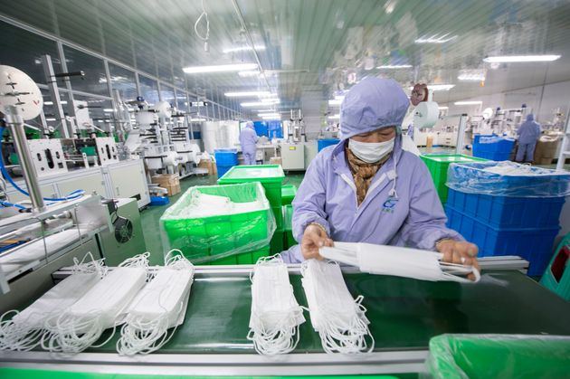 HAI'AN, CHINA - JANUARY 28 2020: A woman worker checks the medical masks at a plant of medical supply...