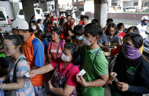 People line up to buy protective face masks at a store in Manila on Thursday after the first coronavirus...