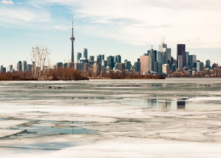 The Toronto skyline is seen here during the winter with melting ice covering Lake Ontario. Research suggests future winters will be warmer and more rainy in Canada's largest city.