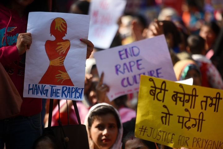 """People hold placards during a sit-in protest as Delhi Commission for Women chairperson Swati Maliwal sits on indefinite hunger strike against the Hyderabad rape and murder. She said, """"I won't get up until I get assurance from centre that rapists will be served death penalty within 6 months. Police accountability needs to be set."""""""