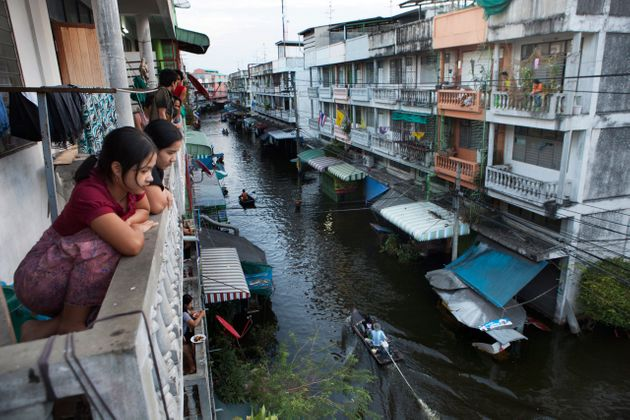 Bangkok residents look down at a flooded street where boats have become the main mode of transport in