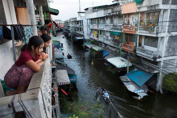 Bangkok residents look down at a flooded street where boats have become the main mode of transport in 2012.