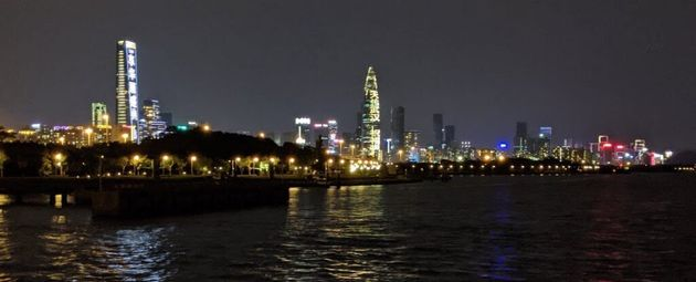 "The Shenzhen skyline at night. The building in the center has projected text that reads ""天佑武汉"