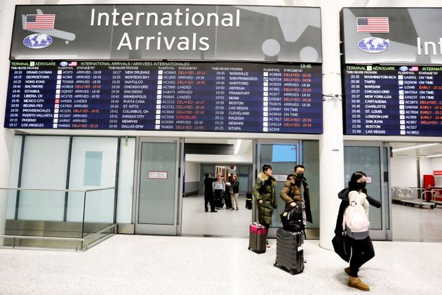 Travellers wear masks at Pearson airport arrivals on Jan.