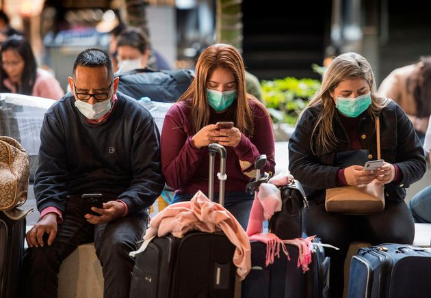 Passengers wear face masks to protect against the spread of the Coronavirus as they arrive on a flight...