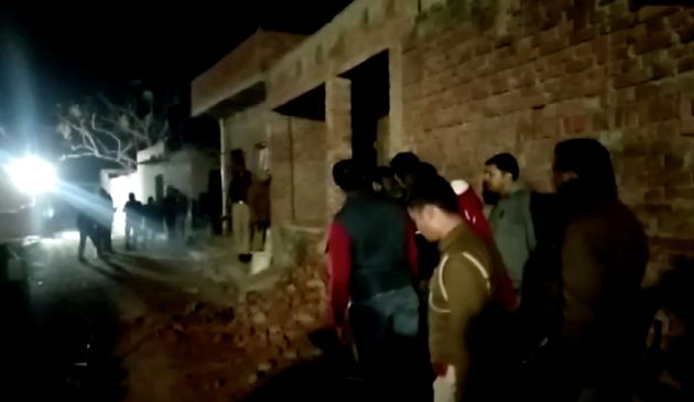 Residents and police personnel stand outside the building where the man held hostages in Farrukhabad,...