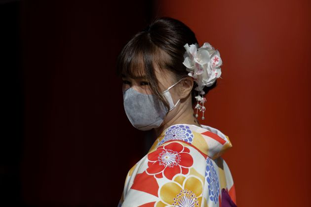 A tourist pauses for photos with her mask on at Sensoji Temple Thursday, Jan. 30, 2020, in Tokyo. The...
