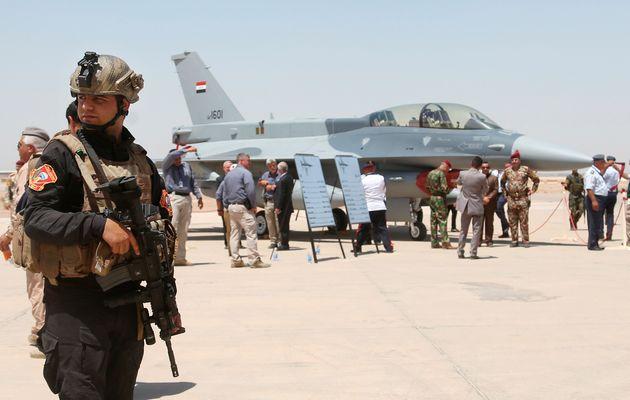 Soldados de Irak, ante una aeronave de EEUU, en la base de Balad, atacada a principios de